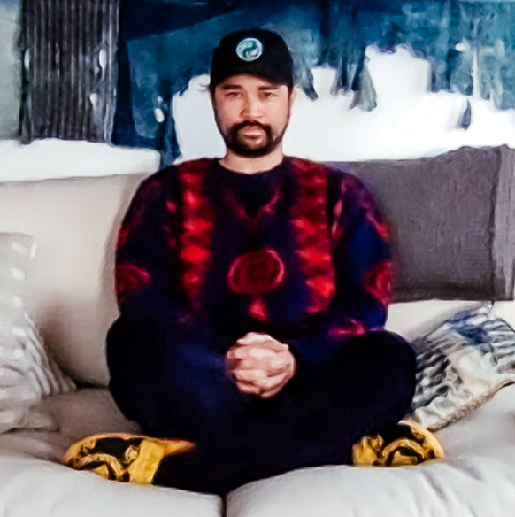 Podcaster James Harris wears a graphic sweater seated on a couch