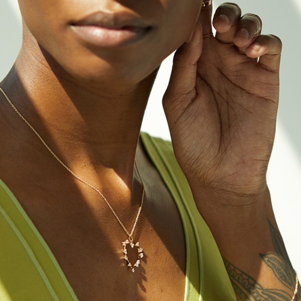 The RealReal x Catbird. Model wearing sustainable jewelry from upcycled collection next to logos