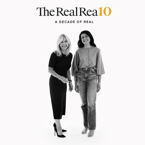 The RealReal founders Julie Wainwright, founder and CEO, and Rati Sahi Levesque, president. Standing together on a white background laughing and smiling. Julie is wearing a black dress and black pumps. Rati wears a grey top with bell sleeves, pale denim jeans, and white strappy sandals.
